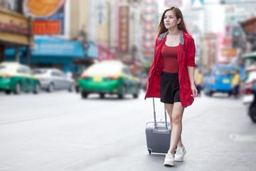 beautiful Young Asian women tourist traveler smiling in red coat walking carrying luggage on the Traffic Road in China town Yaowarat city bangkok thailand.