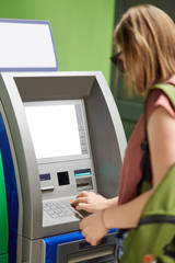Vertical shot of young fashionable girl stands back near cash machine, withdraws money, types on buttons after inserting credit card, enters pin code, uses ATM machine. Finances and money concept.
