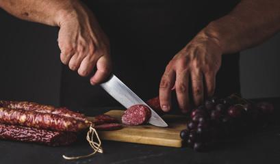 Men's hands cut sausage salami on a cutting board.