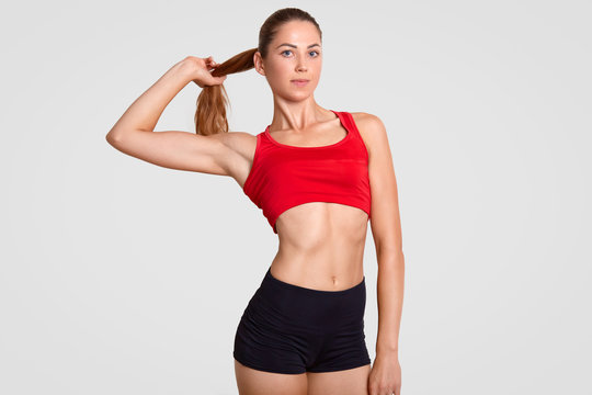 Horizontal shot of slim sporty woman has nice healthy muscular body, dressed in casual top and shorts, touches pony tail, poses against white background. Athletic girl takes break after workout