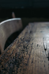 Close up of an old wood table with woodworm signs and scratches