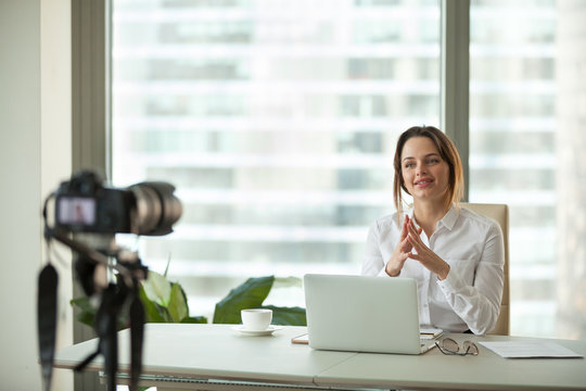 Confident focused businesswoman vlogger talking to camera filming live business vlog concept, friendly female coach advertising online training speaking about success recording video blog in office