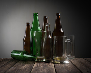 Empty beer glass with bottle caps and bottles on table wood,after party