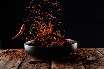 In de dag Kruiden Pouring cayenne pepper powder into the bowl on wood table,Motion blur