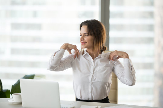 Smiling businesswoman doing easy office exercises to relieve neck and shoulder muscle tension from sedentary computer work, young employee taking break stretching for back relaxation at workplace