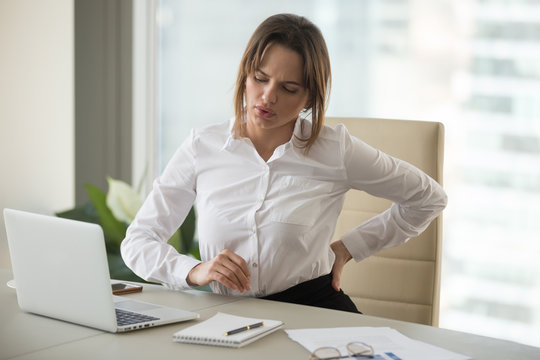 Upset young businesswoman feeling backache touching aching back muscles suffering from low-back lumbar pain sitting in incorrect posture on uncomfortable office chair, sedentary work problems concept