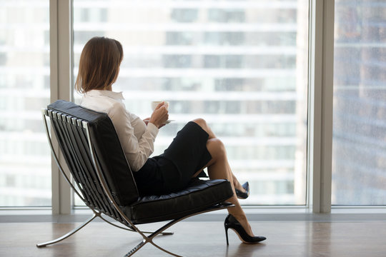 Successful businesswoman sitting in comfortable chair looking out of big window at the city, female boss or rich business lady relaxing enjoying view and morning coffee in modern office or hotel