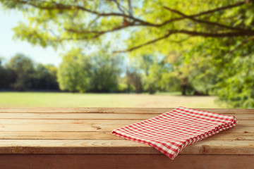 Empty wooden table with tablecloth over autumn nature park background Wall mural