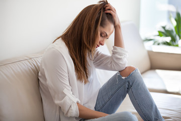Sad depressed thoughtful young woman feeling bad at home, upset millennial lonely girl thinking of sorrow, regrets of mistake or worries about having psychological problem sitting alone on sofa Wall mural