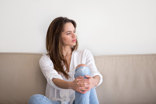 Thoughtful pensive millennial woman sitting on sofa looking away feeling lonely depressed or having problem, melancholic meditative serious girl lost in thoughts, contemplation and reflection concept