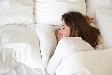 Millennial woman sleeping well on soft pillow and comfortable bed mattress with white cotton sheets under warm duvet having good night sleep enjoying sweet dreams and enough rest concept, top view