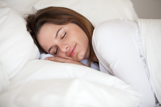 Young woman peacefully sleeping well resting on soft orthopedic pillow in comfortable cozy bed with luxury linen, healthy girl lying asleep on white sheets resting at home or hotel enjoying good nap