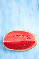 cut Watermelon on blue background. Top view, flat lay.