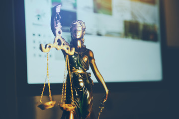 Statue of justice and computer