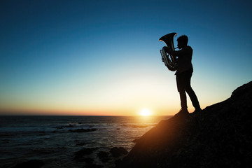 Silhouette of musician play on Tuba on the ocean coast at sunset.