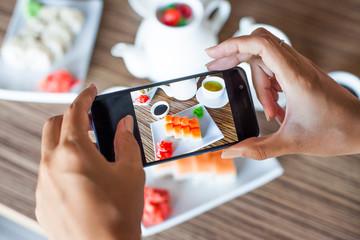 Woman taking photo of tasty sushi set