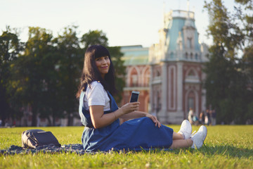 stylish adult woman sits in a beautiful park on green grass and photographs with a smartphone. Moscow, Russia, Park and Palace Tsaritsino