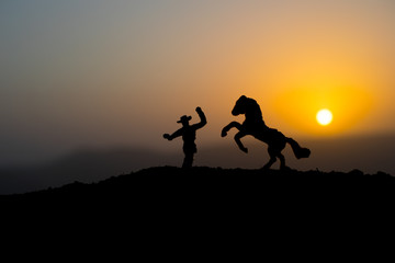 Cowboy concept. Silhouette of Cowboys at sunset time. A cowboy silhouette on a mountain with an yellow sky.