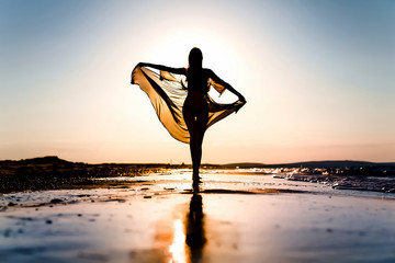 A girl with a transparent handkerchief walks along the beach in the sunset