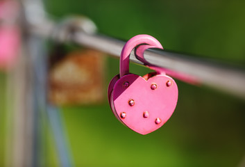 Closed pink heart shaped padlock. Symbol of eternal love. Tradition of lovers on the wedding day. Selective focus.