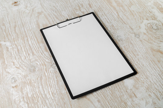 Paper clipboard with blank letterhead on light wooden background with plenty of copy space.