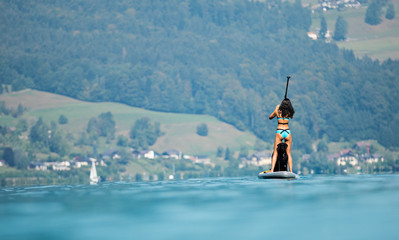 Beautiful woman standing on paddle board with her dog.