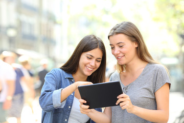 Friends talking about online content in a tablet