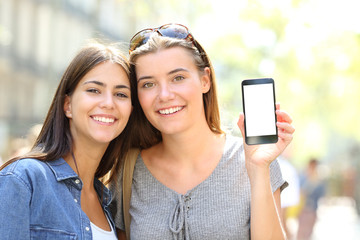 Two happy friends showing a smart phone screen