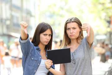 Angry friends holding a tablet with thumbs down