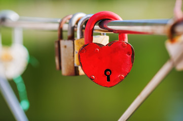 Locked red heart shaped padlock. Symbol of eternal love. Selective focus.