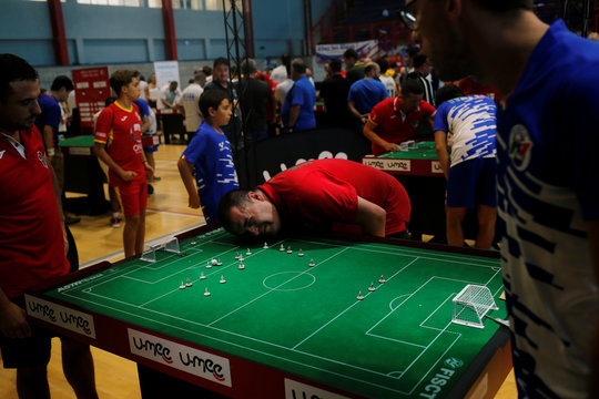 A referee checks the ball during a match of the Open category during the Table Football World Cup in the British overseas territory of Gibraltar