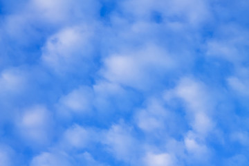 White clouds in the blue, blue sky, a background.