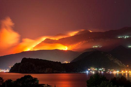 Wild fire blazing on hills above sea town.