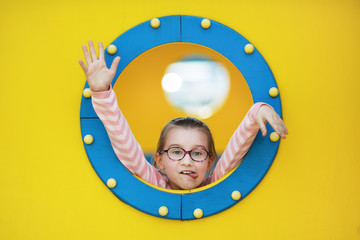 Little baby girl on porthole background. Funny child playing in the playground.