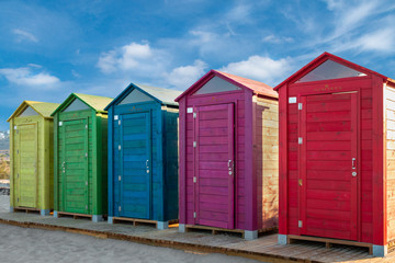 Colorful huts on the beach in Arenales del Sol, Valencia, Spain, Europe. A sunny, holiday day.