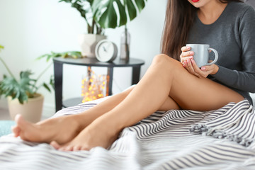 Young woman with sexy legs resting on bed at home