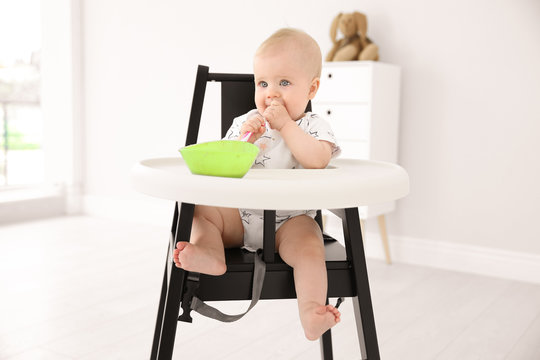 Cute little baby eating in high chair at home