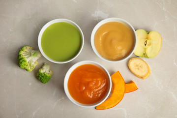 Bowls with different baby food on gray background, flat lay
