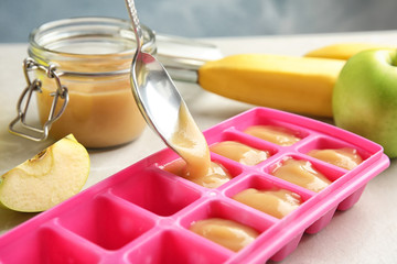 Putting healthy baby food into ice cube tray, closeup