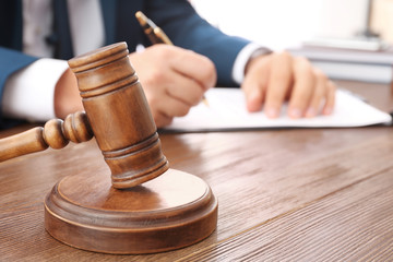 Gavel and blurred lawyer working with documents on background