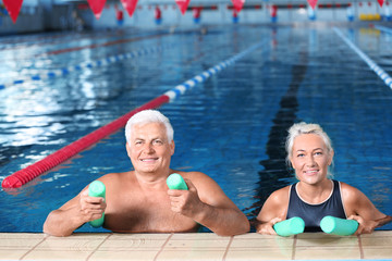 Sportive senior couple with swimming noodles in indoor pool