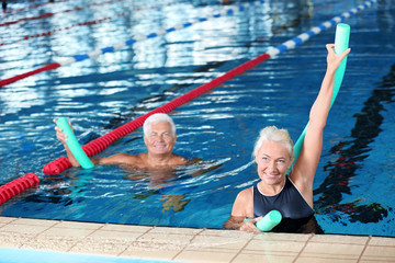 Sportive senior couple doing exercises in indoor swimming pool