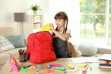Cute girl putting school stationery into backpack at table indoors