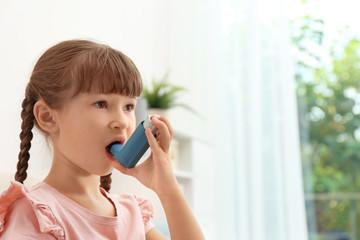 Little girl using asthma inhaler on blurred background