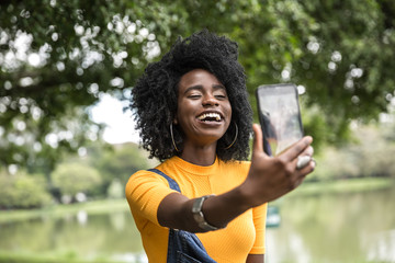 Afro girl taking selfie photos in the park