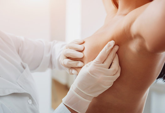 Doctor get examining breast of young woman. Consultation with gynecologist.