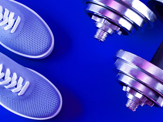 Blue sneakers on ultramarine color background with dumbbells.