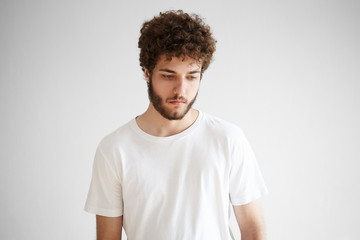 Picture of sad young European male with thick beard looking down having pensive deep in thoughts facial expression, thinking over problems, posing isolated against blank studio wall background