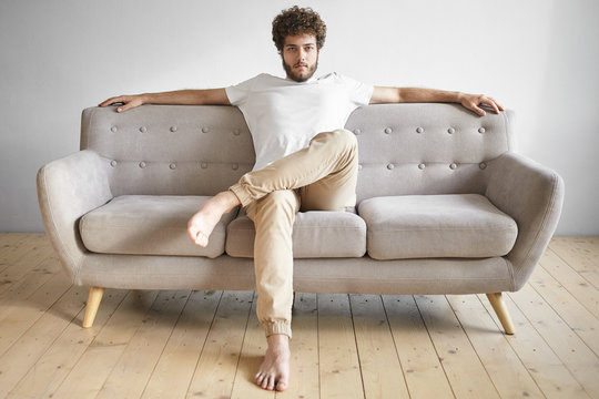 Isolated portrait of fashionable trendy looking young European man with thick beard having rest at home, sitting casually on luxurious sofa, watching TV, feeling relaxed. People, lifestyle and leisure