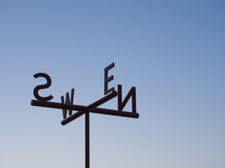 Cardinal Direction (Direction pointer) Sign against blue sky. Directions (North, South, East, West) are denoted by their initials N, E, S, and W on the metal plates.
